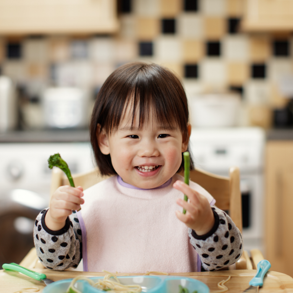 little girl holding veggies smiling
