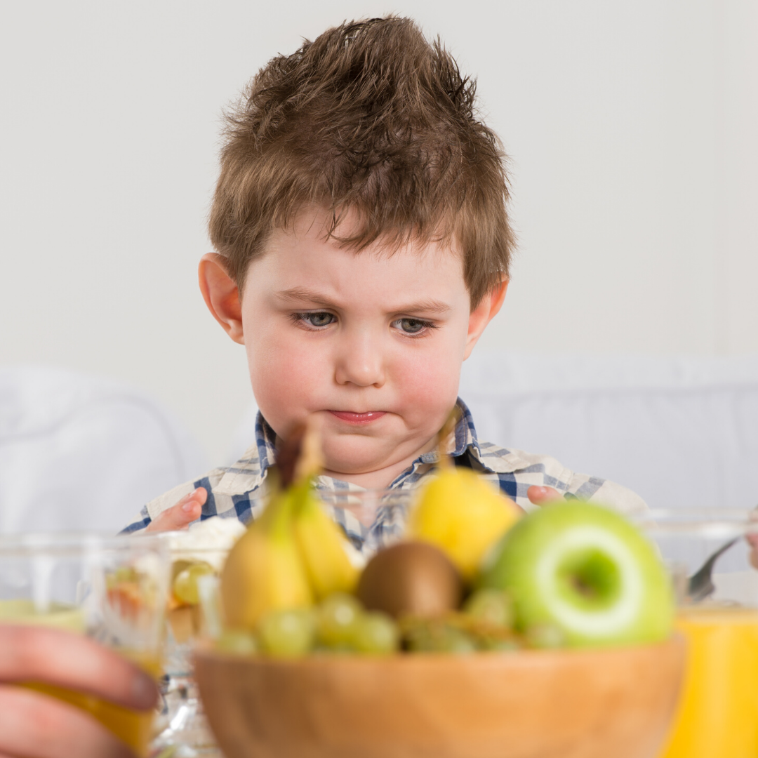 boy looking at bowl of fruit