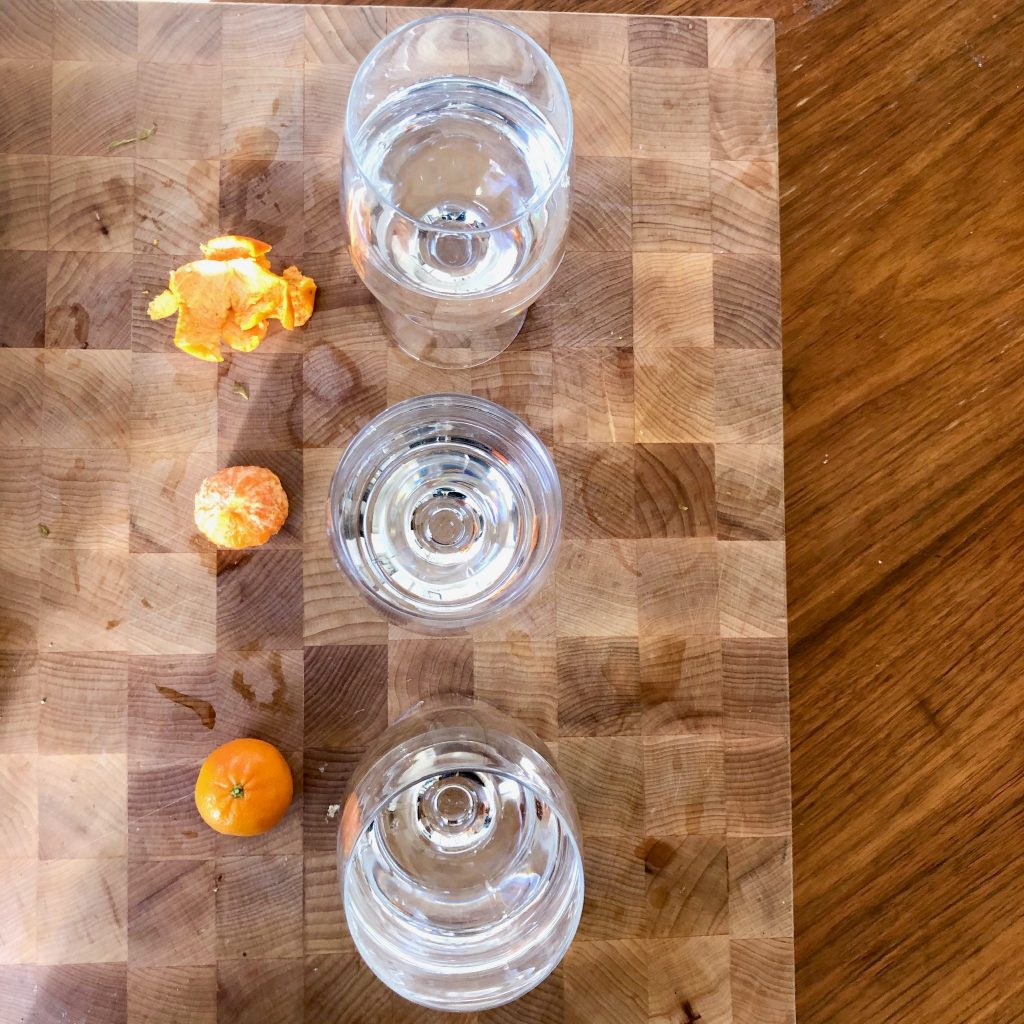 3 glasses of water with a clementine orange, a peel and the peeled orange