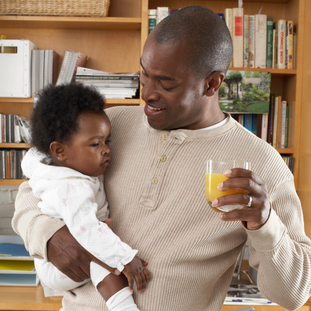 dad holding baby and glass of juice