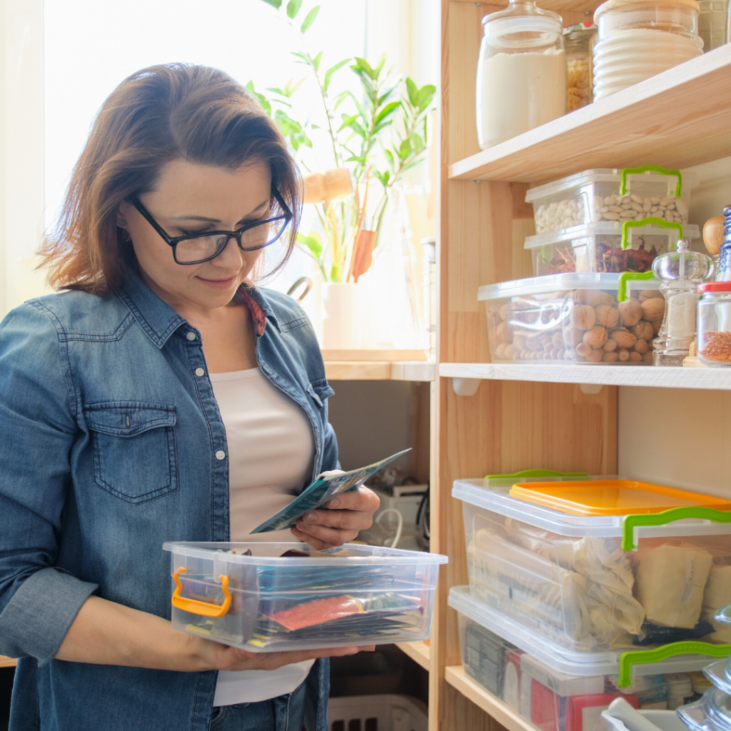 woman in pantry reading food labels