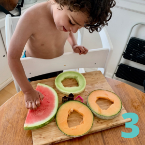 little boy stamping melons into shapes